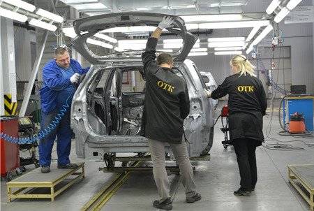 technical department: Staff of checking department checks quality of polishing of a body of the car. Automobile plant