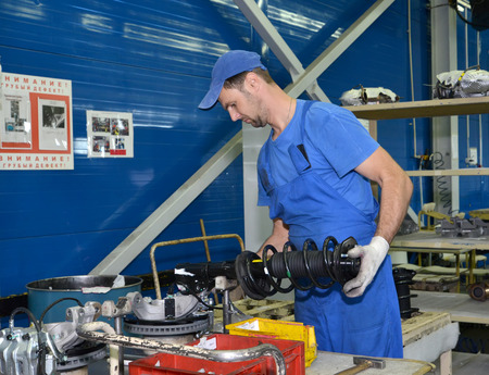 selects: Il lavoratore sceglie rastrelliere di ammortamento per le auto. Negozio Assemblea di fabbrica di automobili