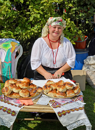 The cheerful woman in a national suit sells rolls at fair of national creativity