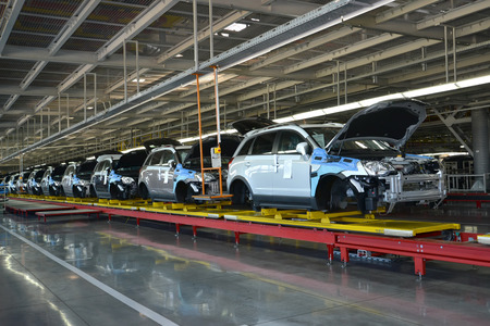 Cars stand on the conveyor line of assembly shop. Automobile production 報道画像