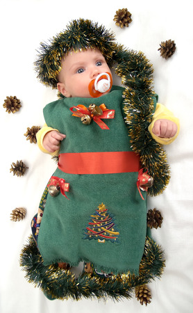 The baby in a New Years suit of a fir-tree on a white  photo