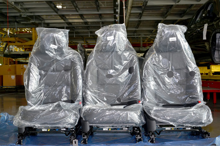 polyethylene film: Automobile chairs in packing stand in assembly shop of automobile plant