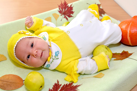 The cheerful baby lies among autumn leaves and fruit Stock Photo