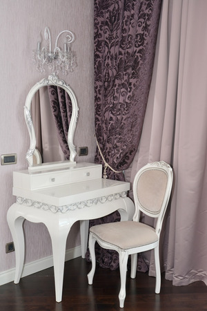 White dressing table and chair in a living room. Modern classics with rococo elements