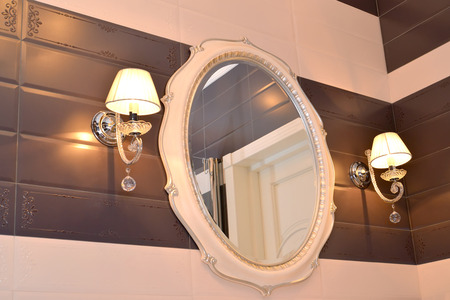 sconces: Mirror and two sconces in a bathroom. Modern classics with rococo elements