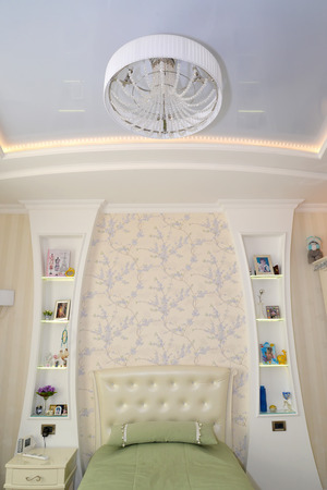 Fragment of an interior of a childrens bedroom in light tones. Modern classics with rococo elements photo