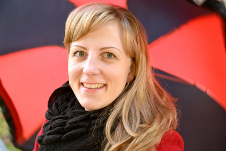 Portrait of the young cheerful woman against a black-red umbrella photo