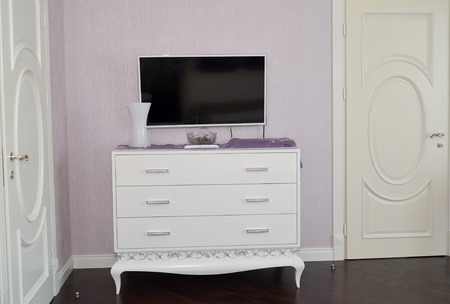 classics: White dresser in a bedroom. Modern classics with rococo elements Stock Photo