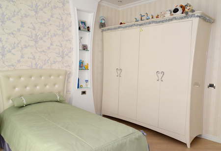 without clothes: Fragment of an interior of a childrens bedroom in light tones. Modern classics with rococo elements
