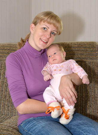 The young woman sits on a sofa with the baby on hands photo