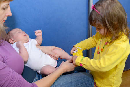 helps: The three-year-old girl dresses bootees on feet to the baby. Close-knit family Stock Photo