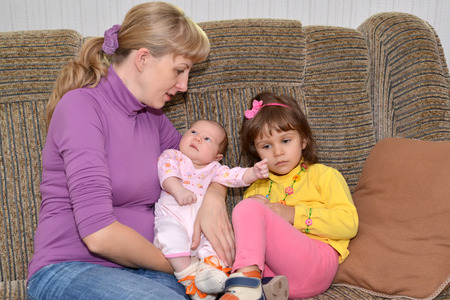 The young woman with two small children sit on a sofa