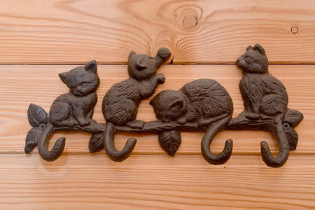 wood molding: Metal hanger with hooks in the form of kittens on a wooden wall Stock Photo