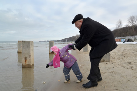 50 to 55 years: The grandfather with the granddaughter throw bread slices into water of the Baltic Sea for feeding of seagulls