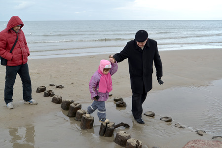 50 to 55 years: The grandfather leads the granddaughter by the hand on old wooden piles on the bank of the Baltic Sea