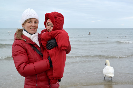Autumn portrait of the young woman with the baby on hands against the Baltic Sea photo