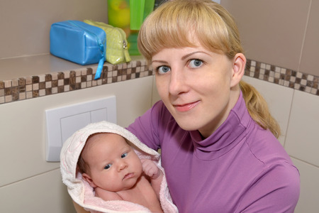 The young woman holds on the babys hands after bathing photo