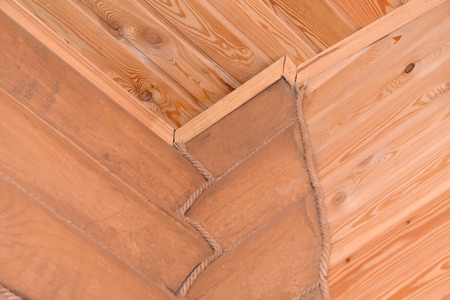 caulk: Timbered laying of the wooden house. Fragment of a corner and ceiling Stock Photo