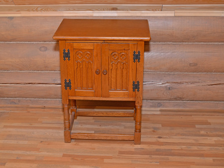 bedside: The wooden bedside table stands near a timbered wall