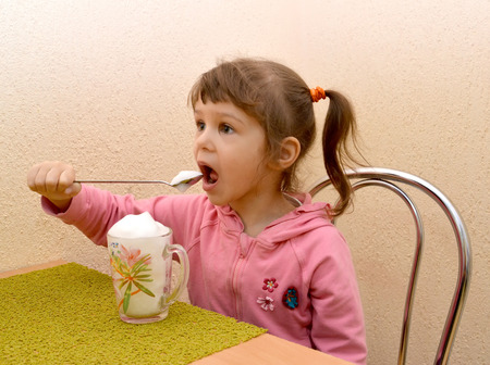 The little girl eats with a spoon oxygen cocktail. Phytobar of childrens sanatorium