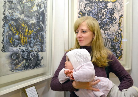 2 5 months: The young woman with the baby consider a picture at an exhibition