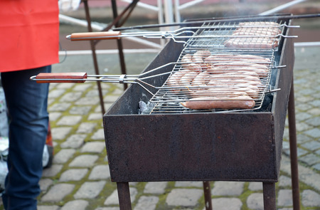 Frying of sausages on a street brazier