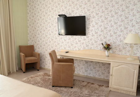 Fragment of an interior of a modern hotel room with upholstered furniture and the TV photo