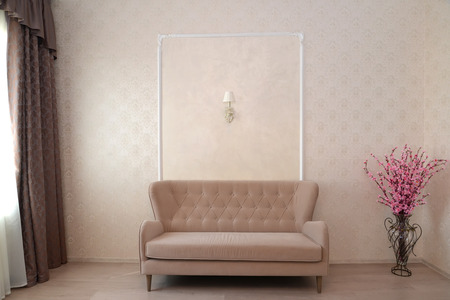 wall sconce: Fragment of an interior of a hotel room with a sofa and a decorative bouquet of an Oriental cherry in a floor vase