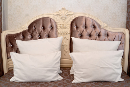 headboard: Carved headboard of a double bed with pillows. Modern classics with rococo elements Stock Photo