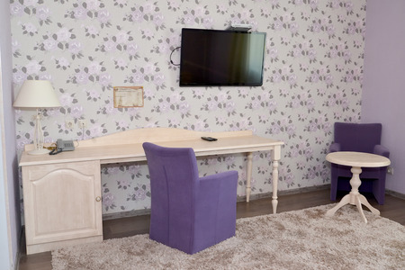 drawing room: Fragment of an interior of a modern hotel room with upholstered furniture and the TV in lilac tones. Drawing room