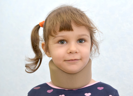 Portrait of the cheerful little girl with an orthopedic collar of Chance on a neck. Medicine Stock Photo