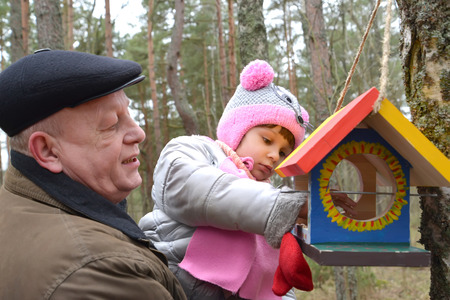 55 years old: The elderly man with the granddaughter put grains in a birds feeder. Family