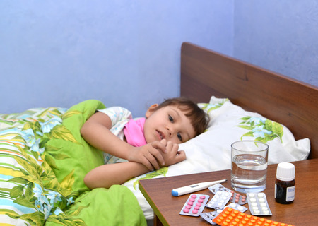 Drugs on a bedside table against the little sick girl lying in a bed. Focus on drugs