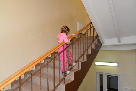overindulgence: The little girl climbs up on a ladder handrail the second floor