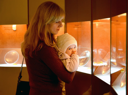 age 30 35 years: The young woman with the baby consider amber exhibits in the museum