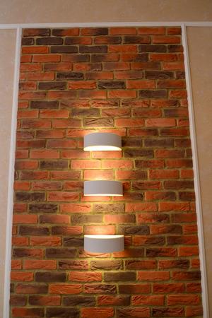 """wall sconce: El panel decorativo de pared """"como el ladrillo"""" con iluminaci�n de una l�mpara de pared en un interior"""