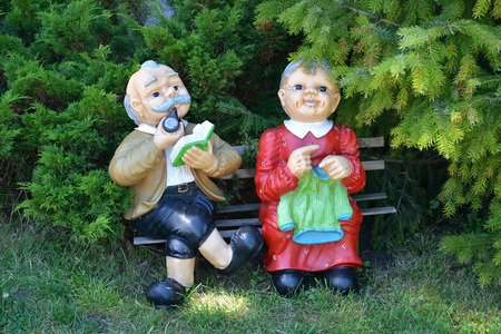 Garden sculpture - the Grandfather and the grandmother sit on a bench in park photo