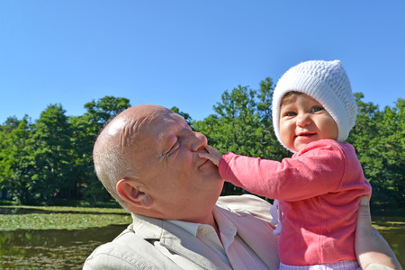 50 to 55 years old: The elderly man keeps on hands the little granddaughter in park