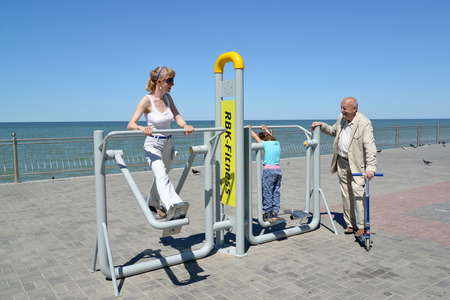 engaged: The young woman with the daughter and the father is engaged on the street exercise machine. Healthy lifestyle Stock Photo