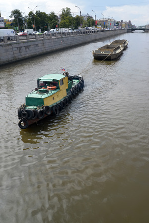 bypass: ST. PETERSBURG, RUSSIA - JULY 23, 2015: The tow pulls gruntootvozny barges on the Bypass channel