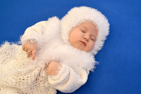babyhood: The sleeping baby in a New Years suit of the Snowflake on a blue background