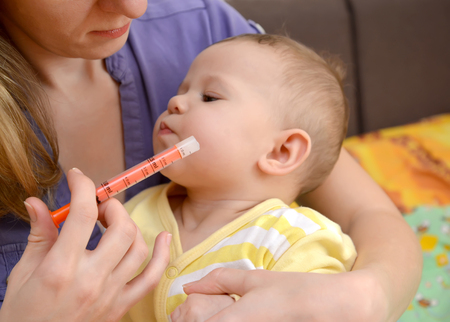 accepts: The sick baby refuses to take medicine by means of the batcher. Treatment Stock Photo