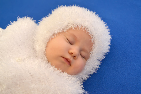 babyhood: The sleeping baby in a New Years suit of the Snowflake on a blue background, a portrait Stock Photo