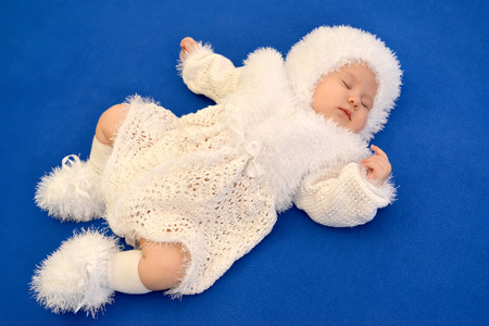 new ages: The sleeping baby in a New Years suit of the Snowflake on a blue background