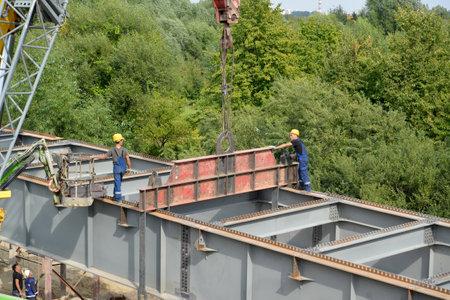 accepts: KALININGRAD, RUSSIA - AUGUST 24, 2015: Slingers establish a metal design. Construction of a road platform