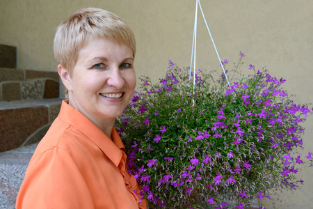 50 to 55 years: Portrait of the woman of average years with decorative flowers a lobelia