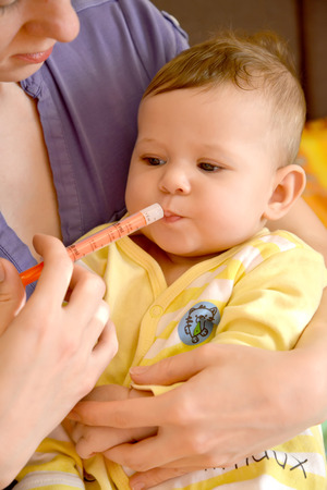 accepts: The woman gives to the sick baby medicine by means of the batcher (flu epidemic) Stock Photo