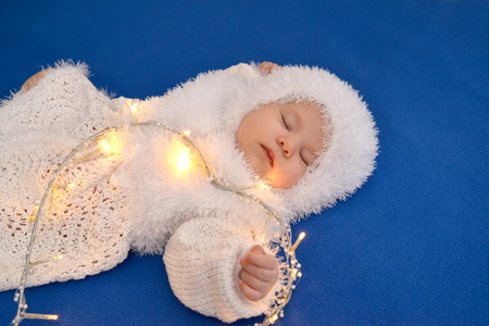 new ages: The sleeping baby in a New Years suit of the Snowflake with the shining garland in the form of heart on a blue background