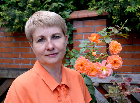 50 to 55 years: Portrait of the woman of average years with roses against a brick protection Stock Photo