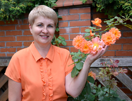 50 to 55 years: The cheerful woman of average years shows a rose hand in a garden Stock Photo